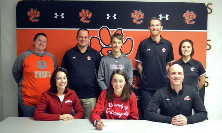 Edwardsville senior Maddie Miller, seated center, is joined by her family and EHS coaches as she signs to compete in cross country and track and field at the University of Indianapolis. Photo: Scott Marion/Intelligencer