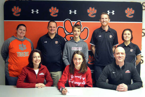 Edwardsville senior Maddie Miller, seated center, is joined by her family and EHS coaches as she signs to compete in cross country and track and field at the University of Indianapolis.