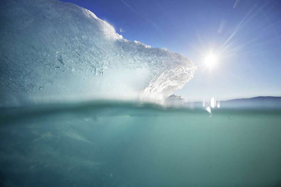 An icebergs floats in the Nuup Kangerlua Fjord near Nuuk in southwestern Greenland, Aug. 1, 2017. Greenland's glaciers have been melting and retreating at an accelerated pace in recent years due to warmer temperatures. If all of that ice melts, sea levels will rise by several meters, though there will be regional differences. Photo: David Goldman /AP / ONLINE_YES