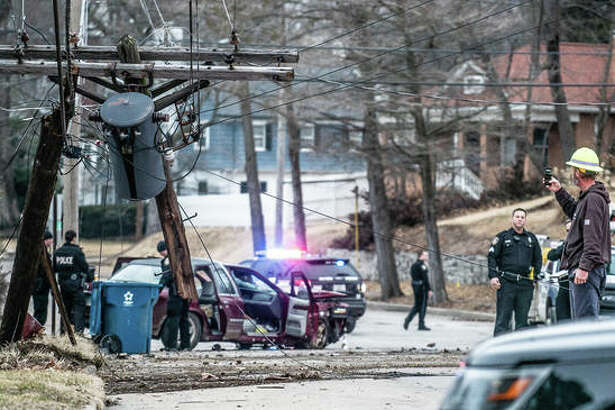 Alton police officers and Ameren crew examine the damage done Thursday after a vehicle fleeing police crashed into a power pole at Liberty and Union streets in Alton.