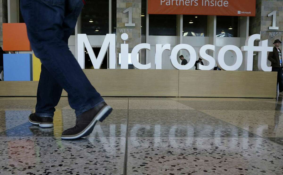 FILE - In this April 28, 2015, file photo, a man walks past a Microsoft sign set up for the Microsoft BUILD conference at Moscone Center in San Francisco. Microsoft reports financial earnings on Thursday, Jan. 28, 2016. (AP Photo/Jeff Chiu, File)