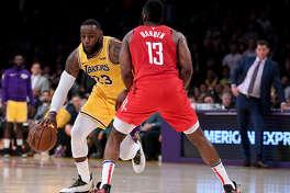 LeBron James (izq.) trata de eludir la marca de James Harden durante el importante triunfo que lograron los Lakers el jueves en el Staples Center de Los Ángeles frente a los Rockets en la reanudación de la NBA.