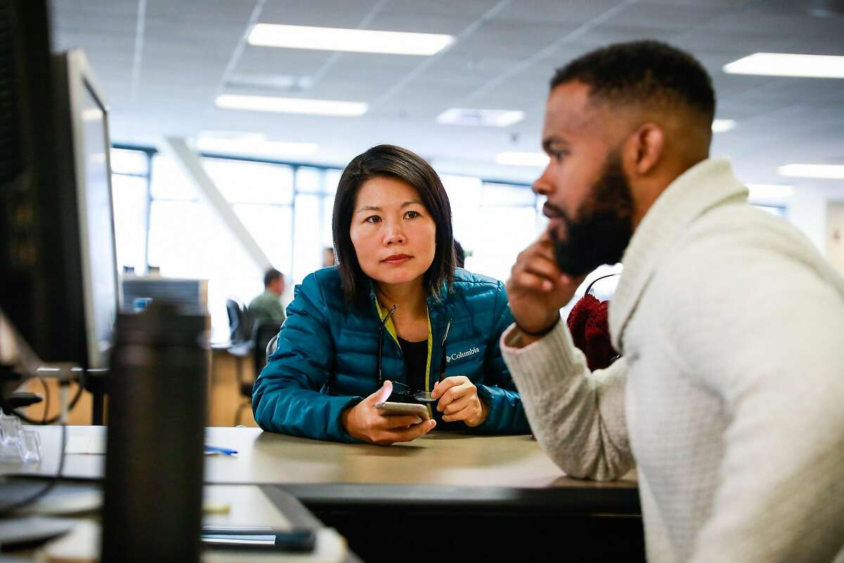 Jingrong Han (left) gets help from Milton Martin at the office of short-term rentals to ask questions about her Airbnb application in San Francisco, California, on Wednesday, Jan. 9, 2019.