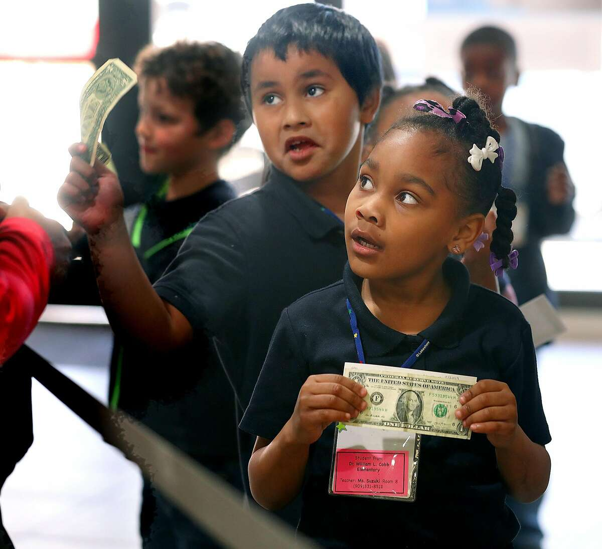 First graders from Cobb Elementary including Kayloni (front) and Daumani (middle) wait in line during a field trip to a Citibank branch to make a deposit to their new savings accounts and learn about banking on Thursday, Feb. 21, 2019, in San Francisco, Calif.