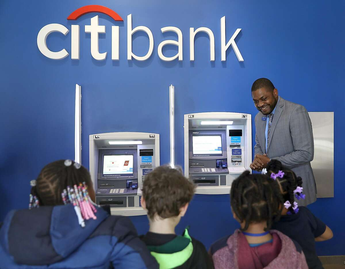 Citibank branch manager Gregory George shows first graders from Cobb Elementary how to use the ATM at his Citibank on Thursday, Feb. 21, 2019, in San Francisco, Calif.