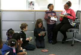 First graders from Cobb Elementary including Jonta and his mom Rufina Gillette (at right) prepare to deposit money at a Citibank branch as the children learn about their new savings accounts and learn about banking during a field trip on Thursday, Feb. 21, 2019, in San Francisco, Calif.