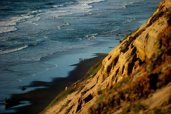 A news crew below at Fort Funston on Friday, Feb. 22, 2019, in San Francisco, Calif. A woman was rescued and another person is still buried and missing after a cliff collapse at Fort Funston.