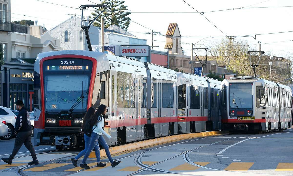 Pedestrians cross in front of trains outside of the West Portal Muni station in San Francisco, Calif. on Friday, Feb. 22, 2019. Traffic officers have been assigned to the intersection of West Portal Avenue and Ulloa Street for the past few weeks to control the often congested flow of cars, trucks, buses and streetcars.