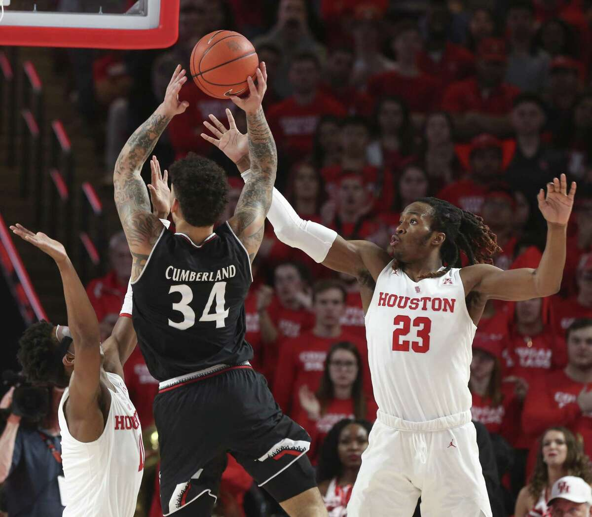 Houston Cougars players Nate Hinton (11) and Cedrick Alley Jr. (23) try to stop Cincinnati Bearcats guard Jarron Cumberland (34) during the second half of the American Athletic Conference game at Fertitta Center on Sunday, Feb. 10, 2019, in Houston. The Houston Cougars defeated the Cincinnati Bearcats 65-58.