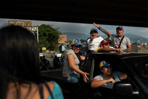 A small group of supporters of the opposition and Juan Guaido shout their support from the back of a truck in San Cristobal, Venezuela on February 21, 2019.