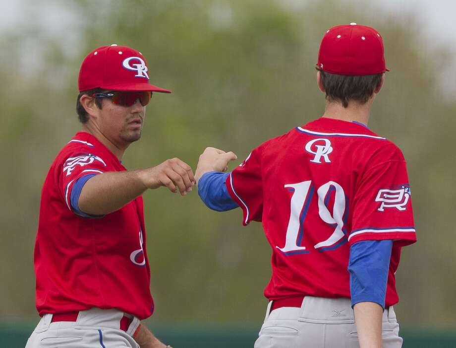 Oak Ridge third baseman Logan Letney, left, gets a fist bump from relief pitcher Colby Wyers after fielding a ground ball by Jacob Prigmore #22 of Montgomery during the fourth inning of a District 12-6A high school baseball game, Saturday, March, 24, 2018, in Montgomery. Oak Ridge defeated Montgomery 12-8. Photo: Jason Fochtman, Staff Photographer / Houston Chronicle / © 2018 Houston Chronicle