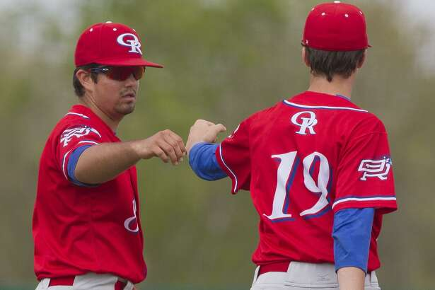 Oak Ridge third baseman Logan Letney, left, gets a fist bump from relief pitcher Colby Wyers after fielding a ground ball by Jacob Prigmore #22 of Montgomery during the fourth inning of a District 12-6A high school baseball game, Saturday, March, 24, 2018, in Montgomery. Oak Ridge defeated Montgomery 12-8.