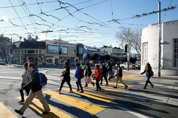 Commuters transfer from a bus to a train at the West Portal Muni station in San Francisco, Calif. on Friday, Feb. 22, 2019. Traffic officers have been assigned to the intersection of West Portal Avenue and Ulloa Street for the past few weeks to control the often congested flow of cars, trucks, buses and streetcars.