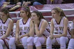 The Mustangs watch on as the last few seconds of a regional semifinal playoff basketball game tick down Friday at the M. O. Campbell Educational Center in Aldine.