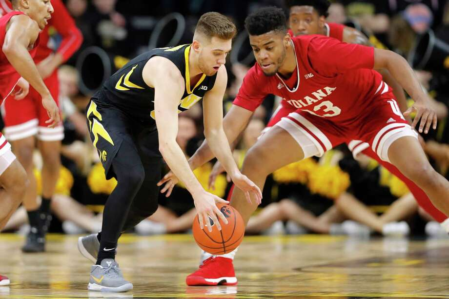 Iowa guard Jordan Bohannon, left, picks up a loose ball in front of Indiana forward Juwan Morgan during the first half of an NCAA college basketball game Friday, Feb. 22, 2019, in Iowa City, Iowa. (AP Photo/Charlie Neibergall) Photo: Charlie Neibergall / Copyright 2019 The Associated Press. All rights reserved