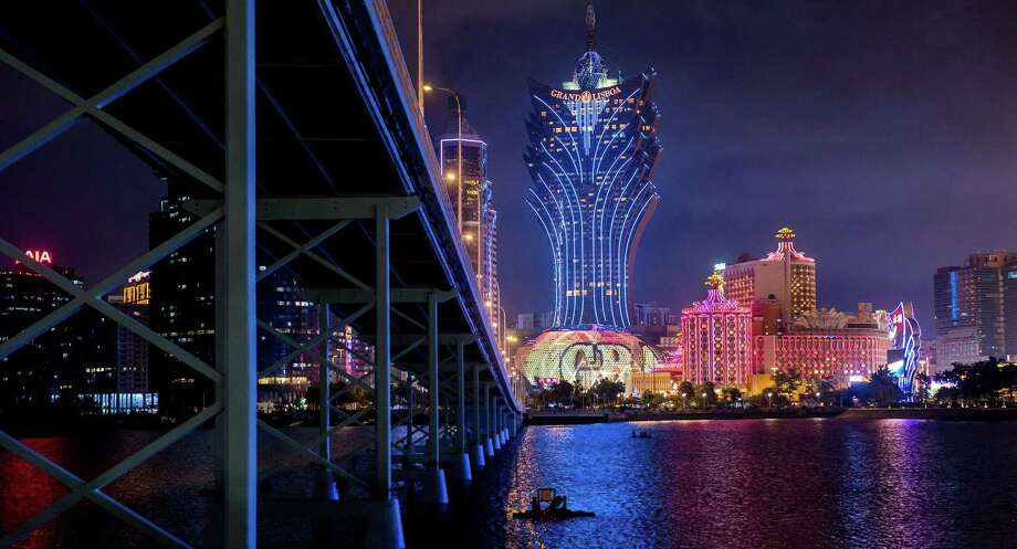 The Macau-Taipa Bridge stands in front of the Casino Grand Lisboa (center) and the Casino Lisboa, both operated by SJM Holdings Ltd., at night in Macau, China, on July 24, 2018. Photo: Bloomberg Photo By Paul Yeung. / 2018 Bloomberg Finance LP