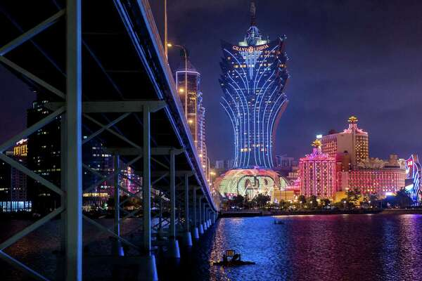 The Macau-Taipa Bridge stands in front of the Casino Grand Lisboa (center) and the Casino Lisboa, both operated by SJM Holdings Ltd., at night in Macau, China, on July 24, 2018.