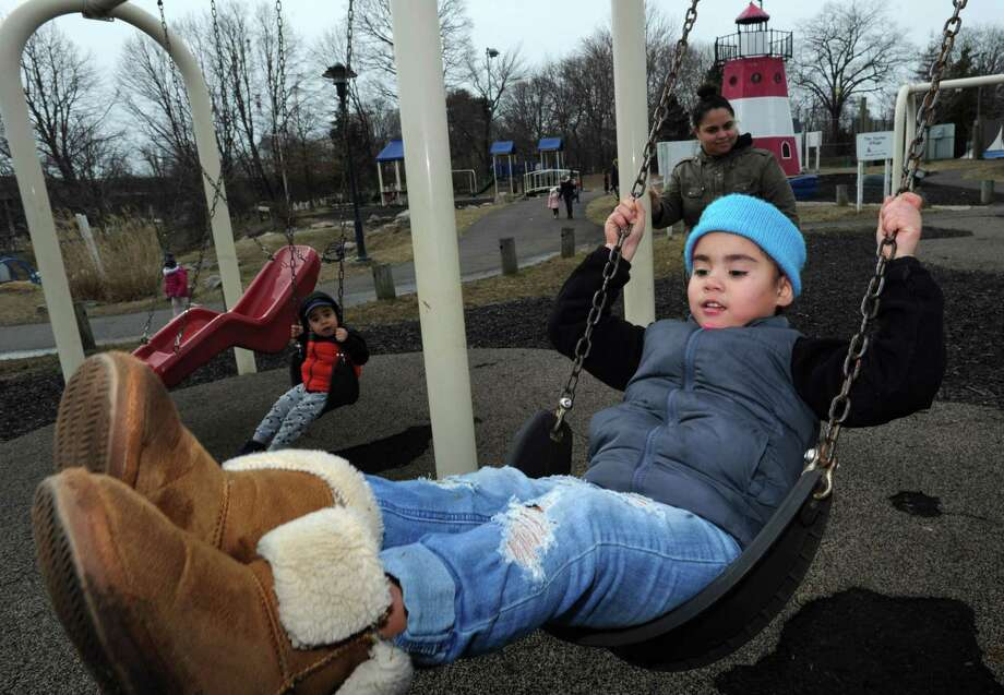 Norwalk resident Angie Tejada watches her daughter Ashlee Tejada, 4, and son, Anthony Tejada, 3, swing at the Devon's Place playground Saturday, February 23, 2019, in Norwalk, Conn. Photo: Erik Trautmann / Hearst Connecticut Media / Norwalk Hour