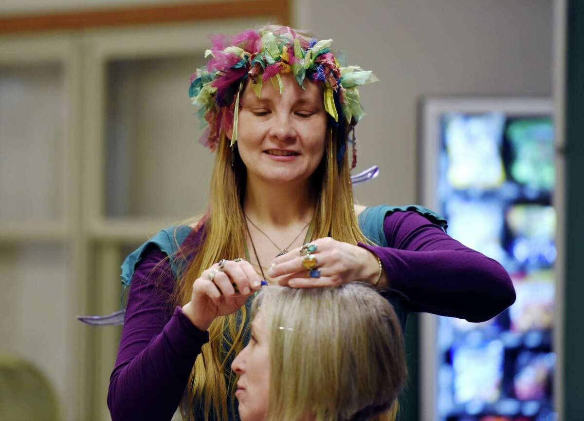 Danielle Seiderer of Faerie Hair Sparkle puts sparkle hair in Carolyn Chevalier's hair during the New York Women's Expo on Saturday, Feb. 23, 2019 at Siena College in Loudonville, NY. (Phoebe Sheehan/Times Union)