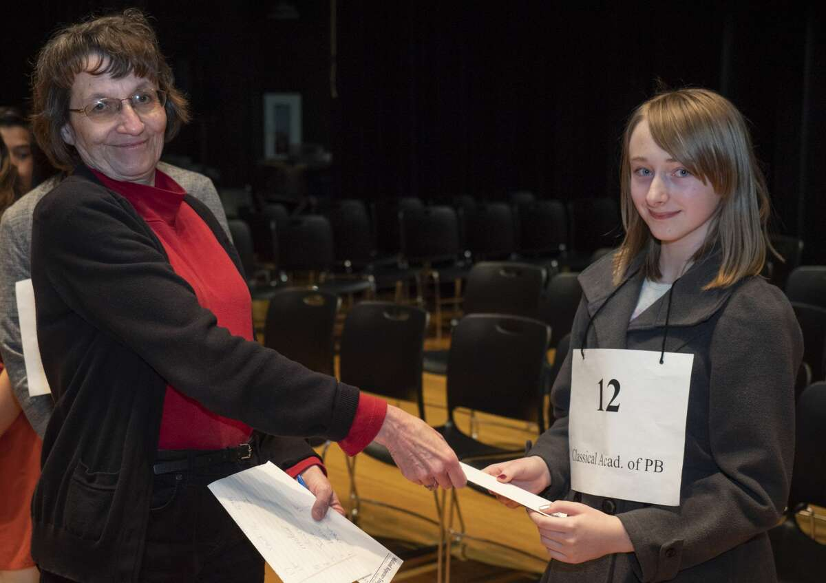 Mary Dearen, Midland Reporter managing editor, awards third place to Jayne Bauer from Midland Classical Academy 02/23/2019 during the 32nd annual Spelling Bee. Tim Fischer/Reporter-Telegram