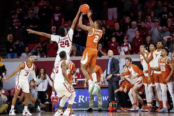 Oklahoma's Jamal Bieniemy (24) blocks a last-second shot by Texas' Matt Coleman III (2) during the second half of an NCAA college basketball game in Norman, Okla., Saturday, Feb. 23, 2019. Oklahoma won 69-67. (Nate Billings/The Oklahoman via AP)