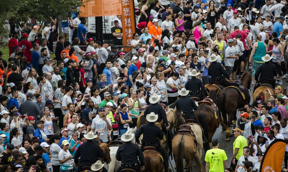 The Harris County Sheriff's Office's deputies ride among the crowd of Rodeo Run runners while everybody little by little find their place before the run and the rodeo parade on Saturday, Feb. 23, 2019, in Houston.