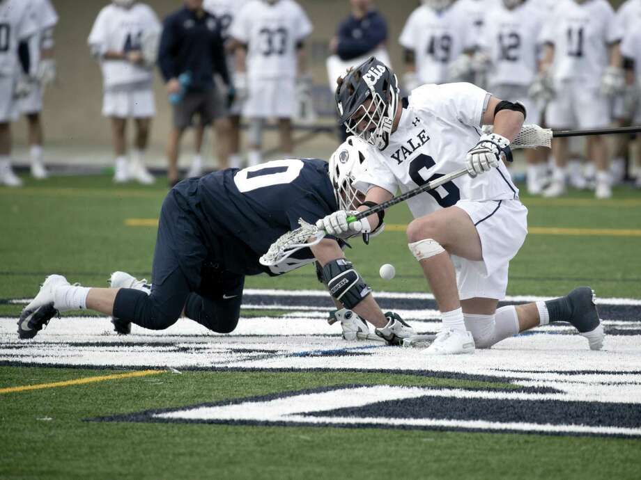 Yale's TD Ierlan in a face-off battle with Penn State's John Nostrant. Photo: Steve Musco / Yale Atheltics / ©2018 - 2019 Steve Musco , All rights reserved