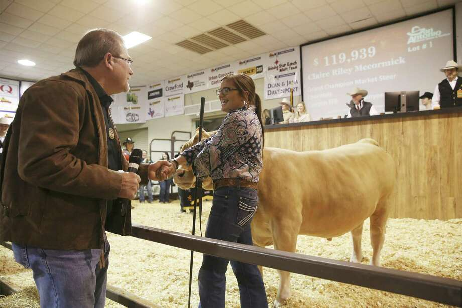 "W.M. ""Rusty"" Rush III, Rush Enterprises' chairman, CEO and president (left) congratulates Claire McCormick after he makes the winning bid of $119,939 for her Grand Champion Steer, a Charolais named Homer, as the San Antonio Stock Show reaches its conclusion with an auction for the winning animals on Saturday, Feb. 23, 2019. Last year's champion earned $110,000 but McCormick's Charolais fetched $119,939 from Rush who made the winning bid in honor of his father, Marvin Rush, who passed away last year. The late Rush was a fixture at the auction. McCormick, a senior at Canyon High, has raised Homer for about a year and only started showing steers five years ago. She hopes to utilize the money to further her education and go into the field of radiography. (Kin Man Hui/San Antonio Express-News) Photo: Kin Man Hui, Staff Photographer / San Antonio Express-News / ©2019 San Antonio Express-News"