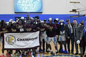 Members of the Albertus Magnus men's basketball team hold up the championship banner after beating St. Joseph to win the GNAC championship Saturday.