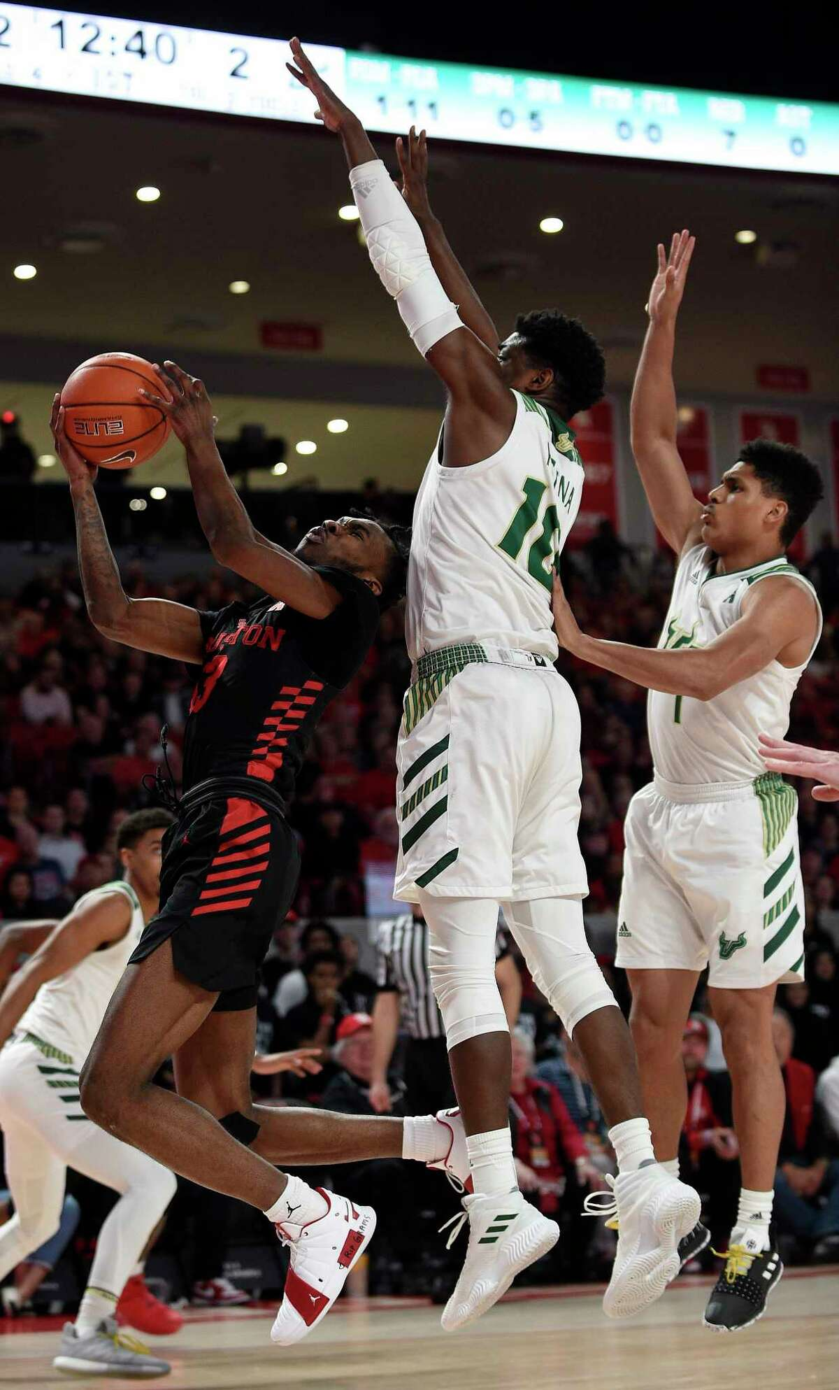 Houston guard Armoni Brooks (3) drives to the basket as South Florida forward Alexis Yetna, center, defends during the first half of an NCAA college basketball game, Saturday, Feb. 23, 2019, in Houston.