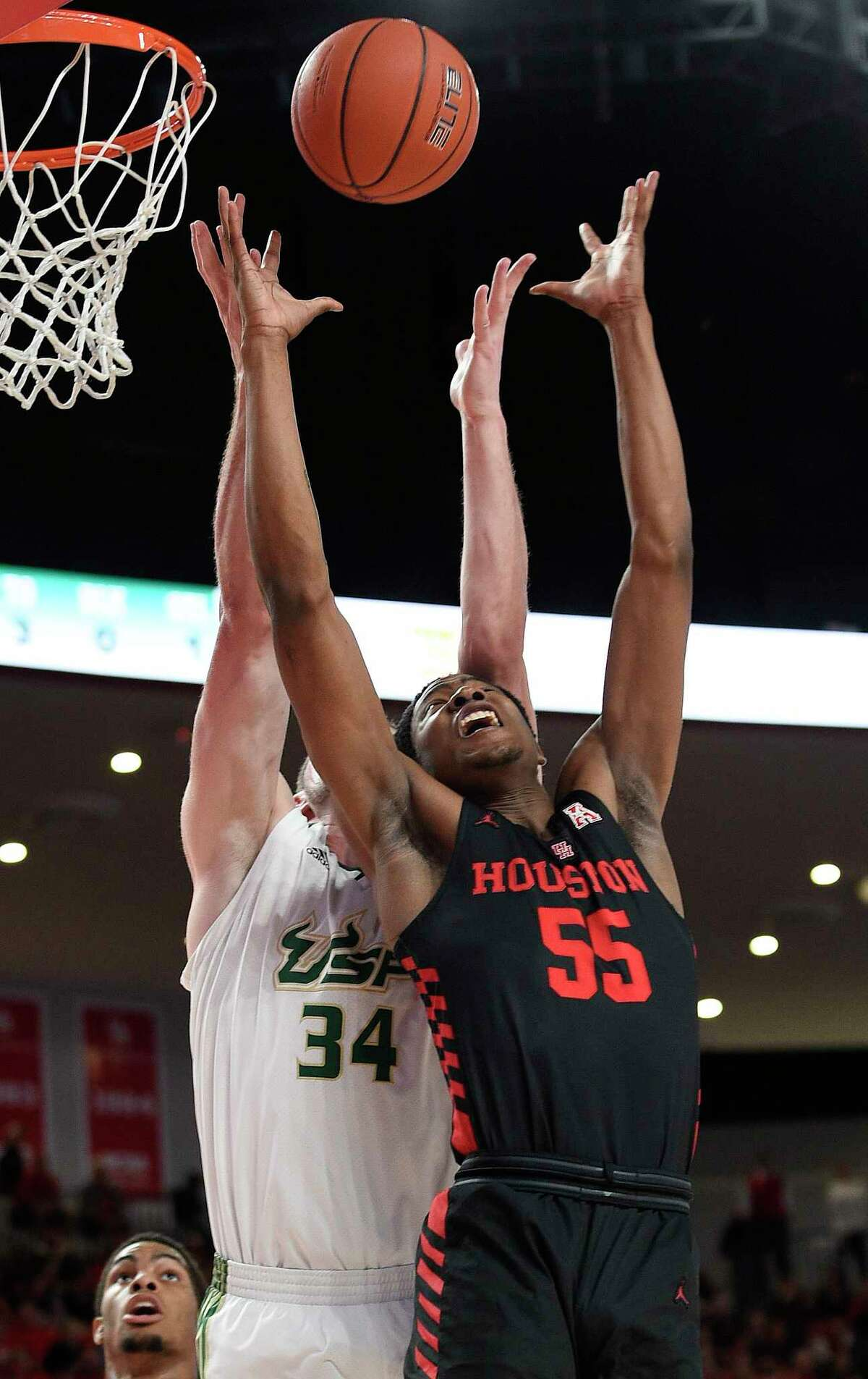 Houston forward Brison Gresham (55) and South Florida forward Antun Maricevic (34) reach for a rebound during the first half of an NCAA college basketball game, Saturday, Feb. 23, 2019, in Houston.