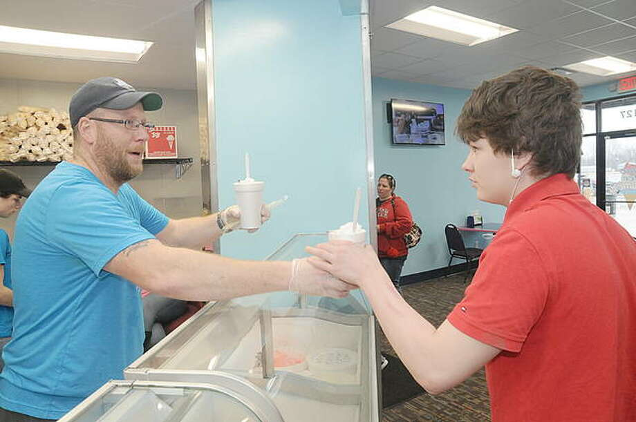 Blue Ice Creamery owner Kyle Shirley serves Eli Shores of Hartford. Photo: David Blanchette | For The Telegraph