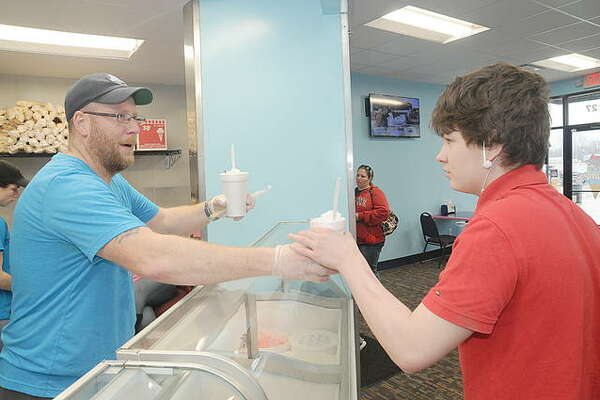 Blue Ice Creamery owner Kyle Shirley serves Eli Shores of Hartford.