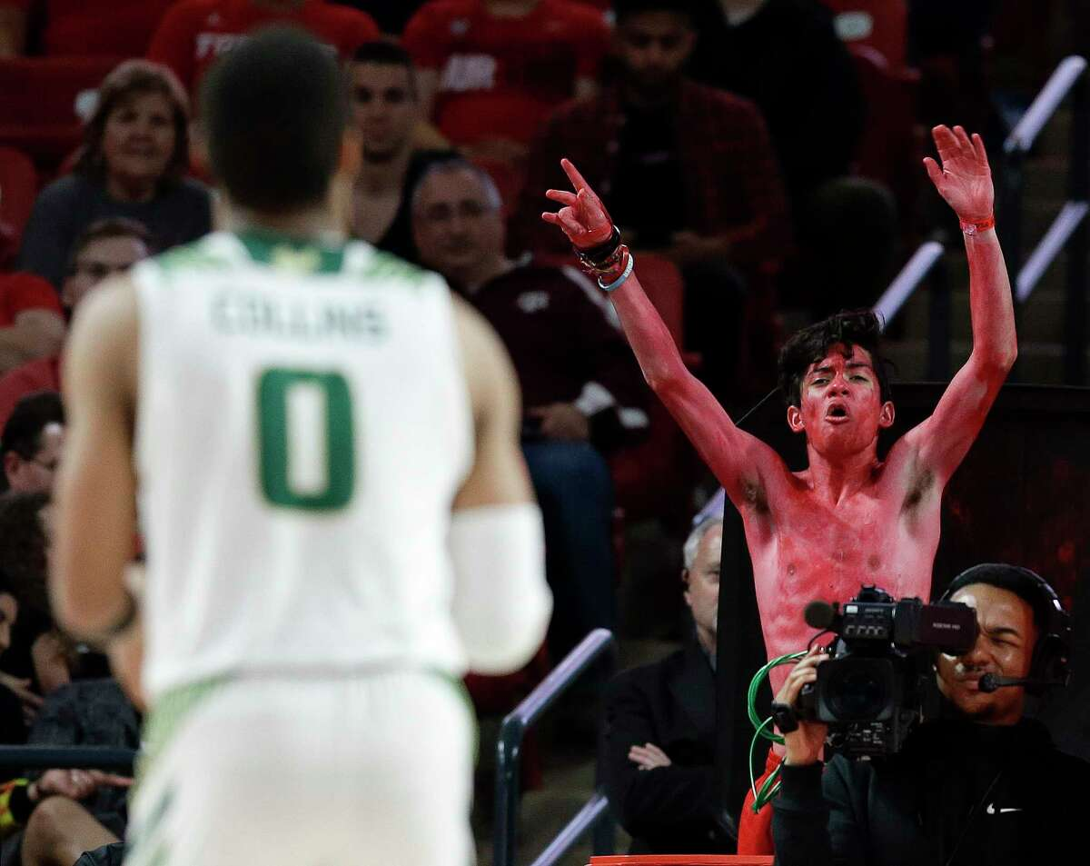 Houston fan Luis Lemus, top right, tries to distract South Florida guard David Collins during a free-throw attempt.