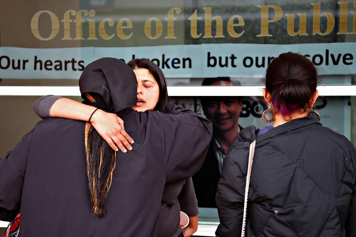 People who declined to give their names embrace in front of the Office of the Public Defender following a memorial for San Francisco Public Defender Jeff Adachi in San Francisco on Saturday Feb. 23, 2019.