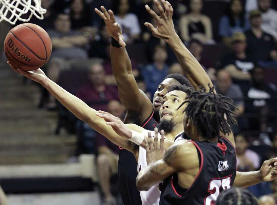 Bobcat junior Nijal Pearson stretches his layup in past Jerekius Davis,top, and Jakeenan Gant in the second half as Texas State hosts Louisiana in men's basketball at Strahan Arena on February 23, 2019. Photo: Tom Reel, Staff / Staff Photographer / 2019 SAN ANTONIO EXPRESS-NEWS