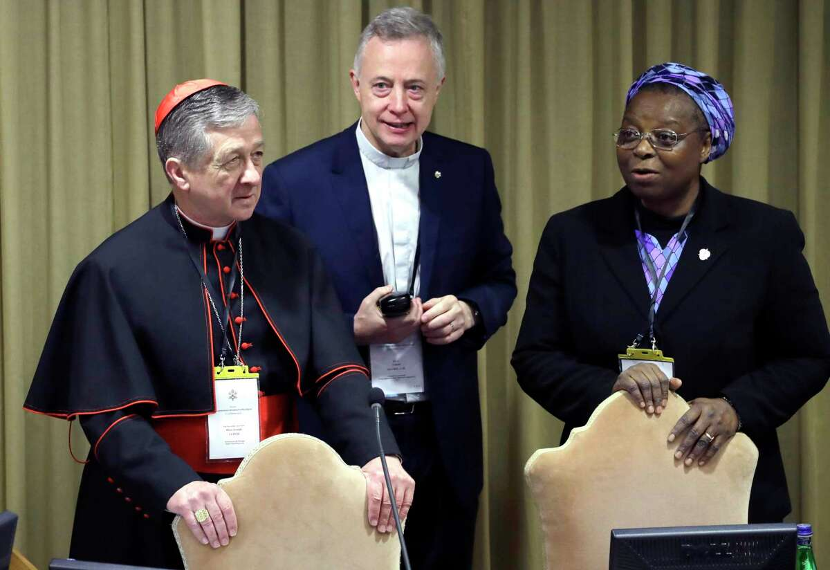 Sister Veronica Openibo, right, stands next to Chicago Archbishop Cardinal Blase J. Cupich, left, and Father Tomaz Mavric, center, as they wait for Pope Francis to arrive at the third day of a Vatican's conference on dealing with sex abuse by priests, at the Vatican, Saturday, Feb. 23, 2019. The prominent Nigerian nun has blasted the culture of silence in the Catholic Church that has long sought to hide clergy sexual abuse, telling a Vatican summit that transparency and an admission of mistakes is needed to restore trust. (AP Photo/Alessandra Tarantino, Pool)