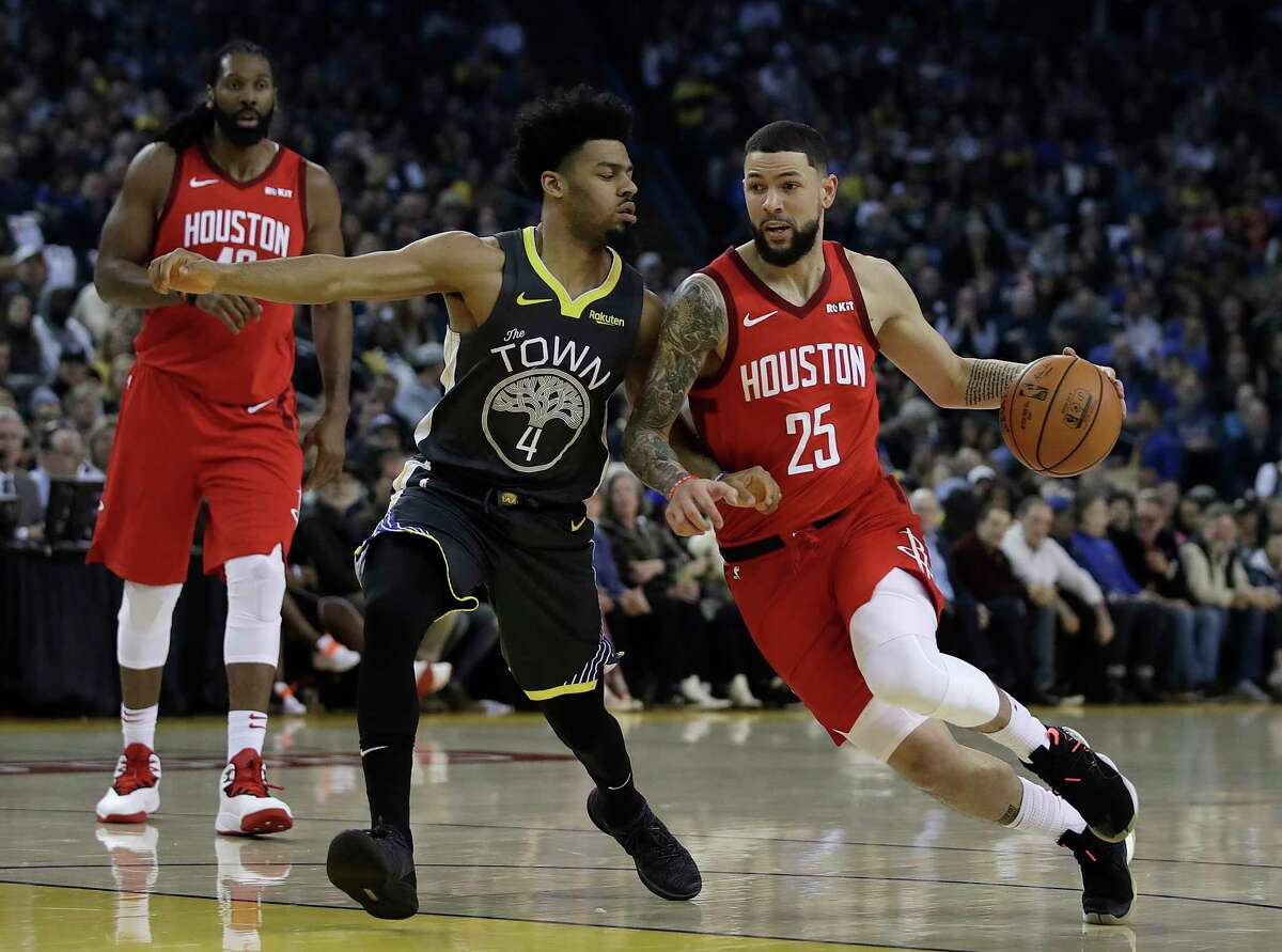 Houston Rockets' Austin Rivers, right, drives the ball against Golden State Warriors' Quinn Cook, left, during the first half of an NBA basketball game Saturday, Feb. 23, 2019, in Oakland, Calif. (AP Photo/Ben Margot)