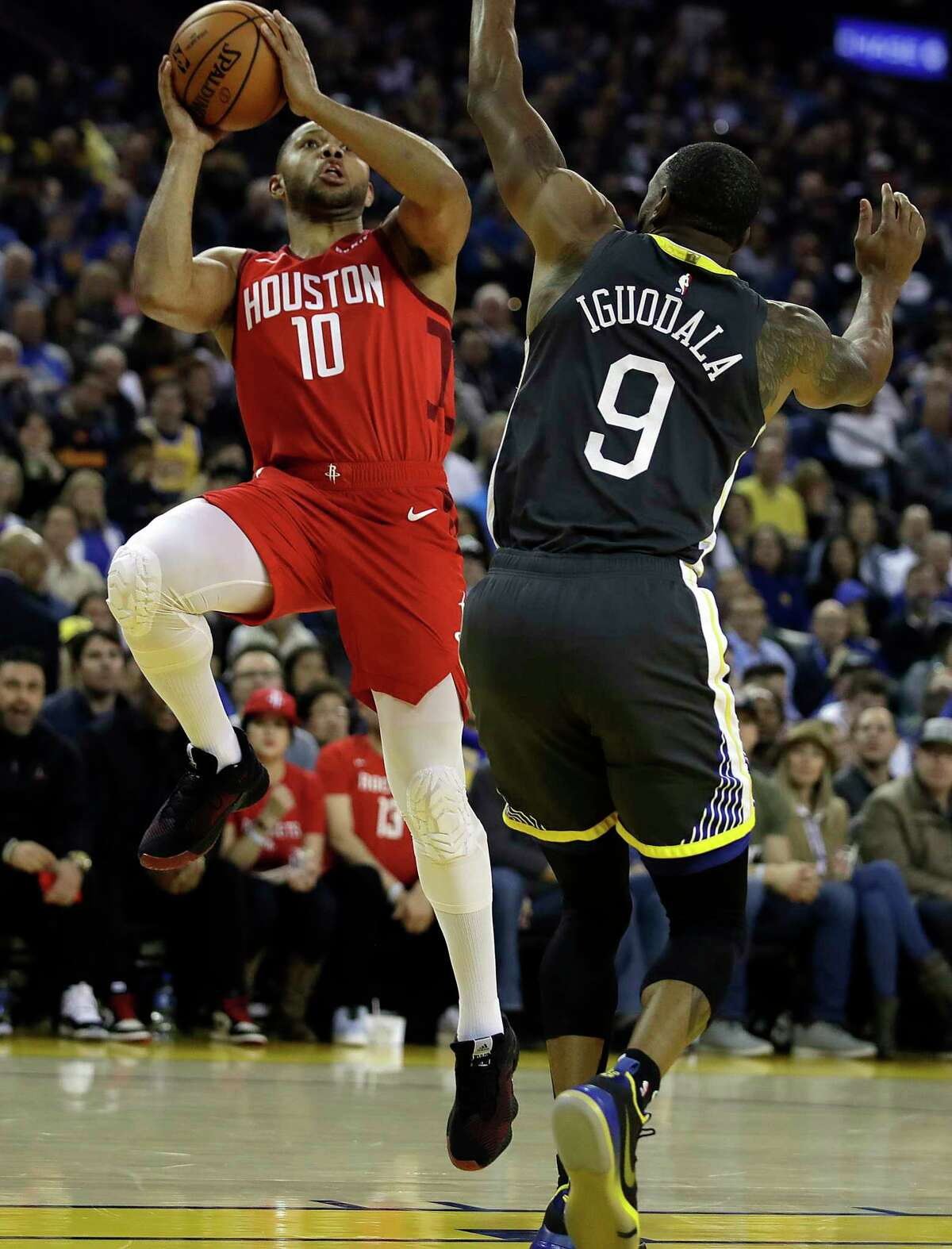 Houston Rockets' Eric Gordon, left, drives the ball against Golden State Warriors' Andre Iguodala, right, during the first half of an NBA basketball game Saturday, Feb. 23, 2019, in Oakland, Calif. (AP Photo/Ben Margot)