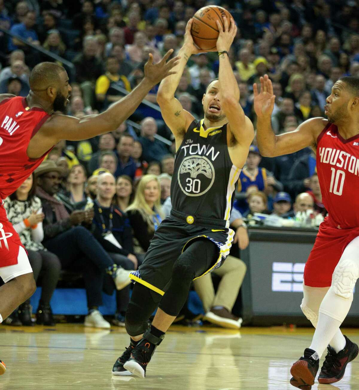 Golden State Warriors guard Stephen Curry (30) drives between Houston Rockets guard Chris Paul (3) and forward Eric Gordon (10) during the second quarter of an NBA basketball game on Saturday, Feb. 23, 2019 in Oakland, Calif.