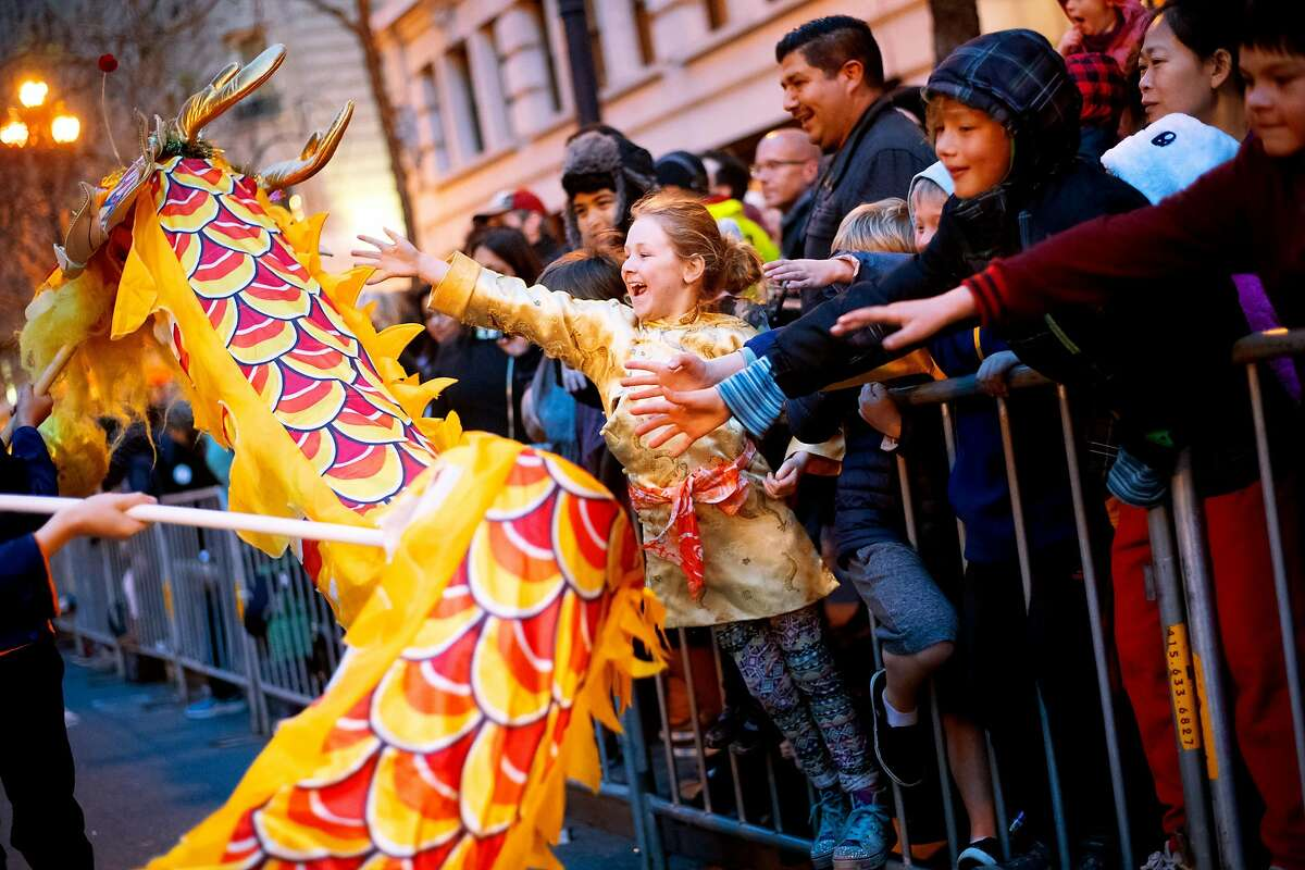 Elisabeth Milich, 7, reaches to touch a dragon during San Francisco's annual Chinese New Year Parade on Saturday, Feb. 23, 2019.