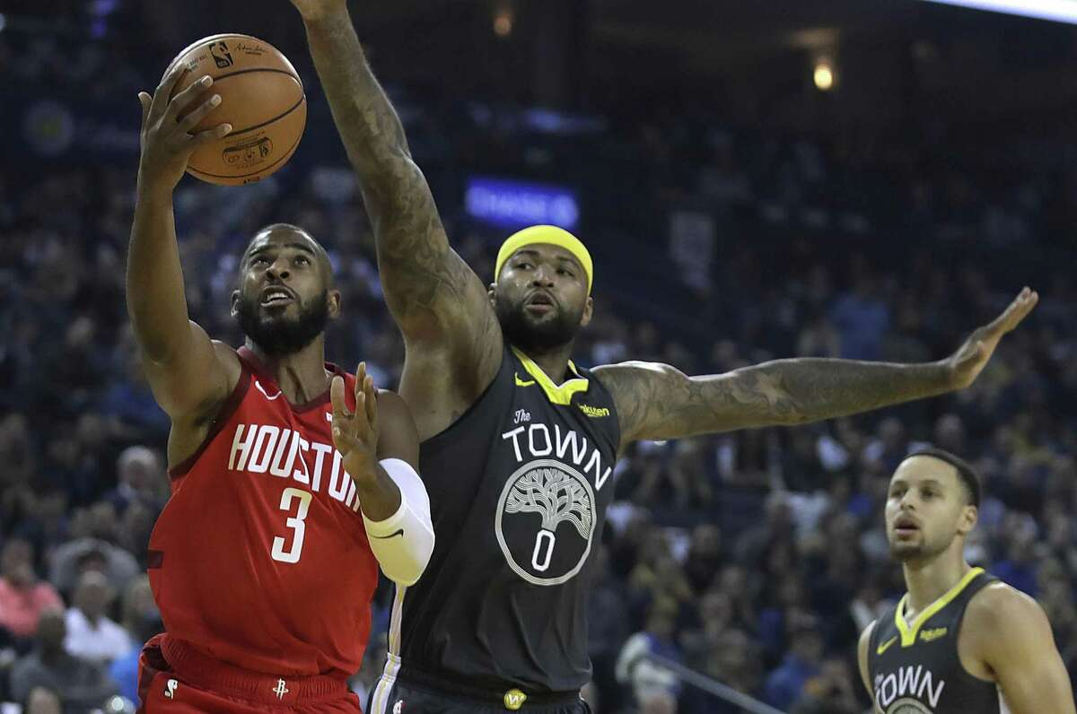The Rockets' Chris Paul, left, drives past the Warriors' DeMarcus Cousins, center, in the first half of the Rockets' 118-112 win Saturday. Paul had 23 points and 17 assists.