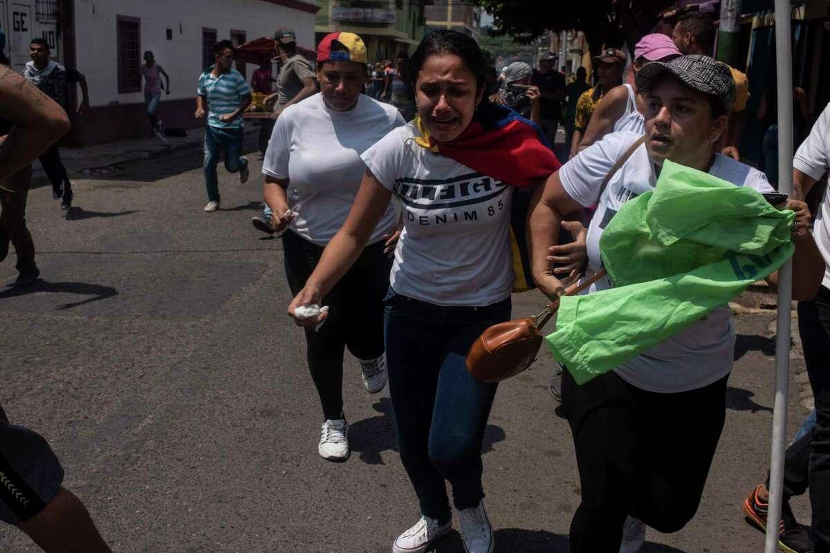 Women run from armed pro-government militias on motorcycles in San Antonio, Venezuela, on Saturday.