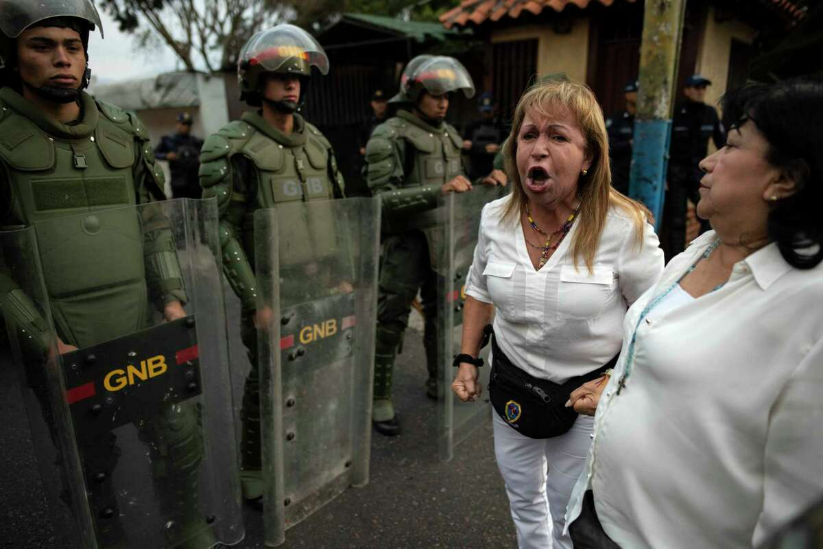 A woman yells about her lack of medicine beside a blockade of National Guard troops in Capacho, Venezuela, on Saturday.