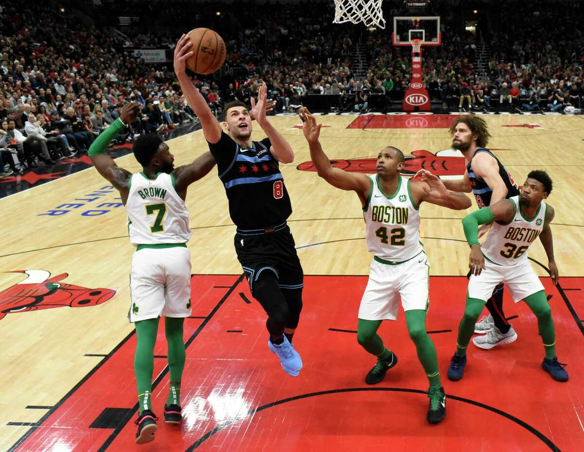 Chicago Bulls guard Zach LaVine (8) goes up for a shot as Boston Celtics guard Jaylen Brown (7) and center Al Horford (42) defend him during the second half of an NBA basketball game Saturday, Feb. 23, 2019, in Chicago. The Bulls won 126-116. (AP Photo/David Banks)