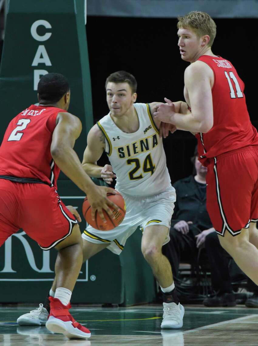 Jimmy Ratliff of Siena, center, tries to stop Brian Parker from driving to the basket during their game against Marist on Sunday, Feb. 24, 2019, in Albany, N.Y. (Paul Buckowski/Times Union)