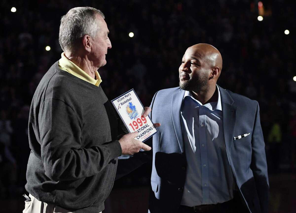 Former UConn coach Jim Calhoun, left, presents former player Khalid El-Amin with a plaque during a halftime ceremony honoring the 1999 national championship team Feb. 24 in Hartford.