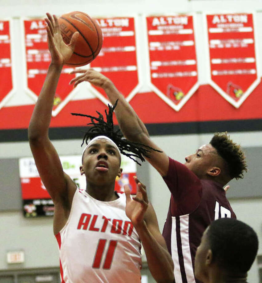 Alton's Donovan Clay (11) has his shot in the lane blocked by Belleville West's Tommie Williams during the fourth quarter of the Redbirds' SWC victory Tuesday at Alton High in Godfrey. The Redbirds take a 21-10 record to this week's Collinsville Class 4A Regional. Photo: Greg Shashack / The Telegraph