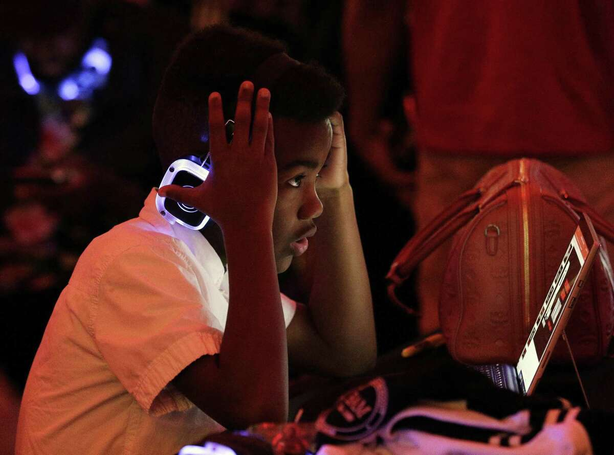 H. Stern, age 10, gestures as he listens to music on glowing headphones during a joint program between Reading With A Rapper (RWAR) and My Brother's Keeper Houston (MBK) in the Legacy Room at City Hall Sunday, Feb. 24, 2019 in Houston, TX.