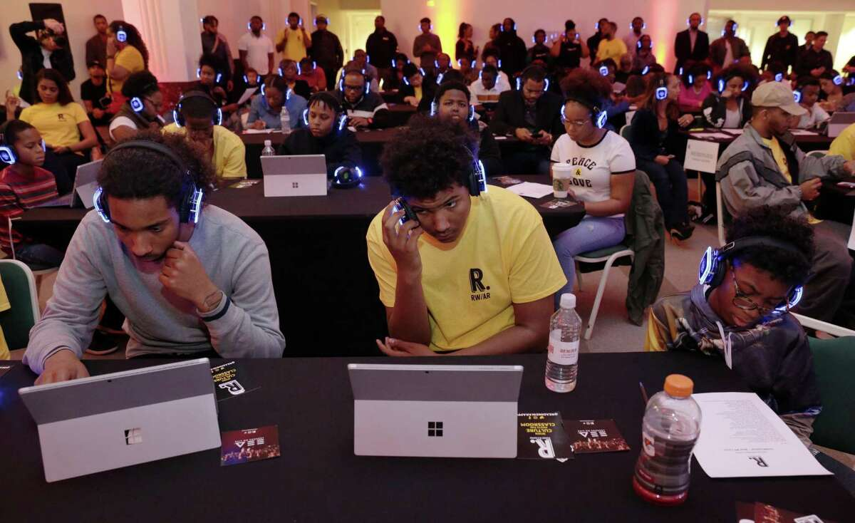 Attendees listen to music on glowing headphones using smart pads during a joint program between Reading With A Rapper (RWAR) and My Brother's Keeper Houston (MBK) in the Legacy Room at City Hall Sunday, Feb. 24, 2019 in Houston, TX.